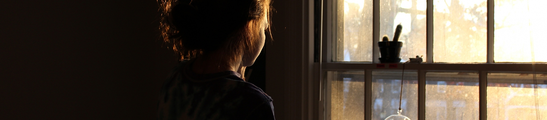 A women looking out of a window towards the light