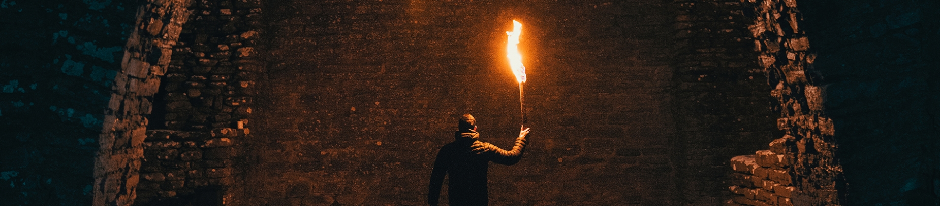 A man holding a flame up to a brick wall