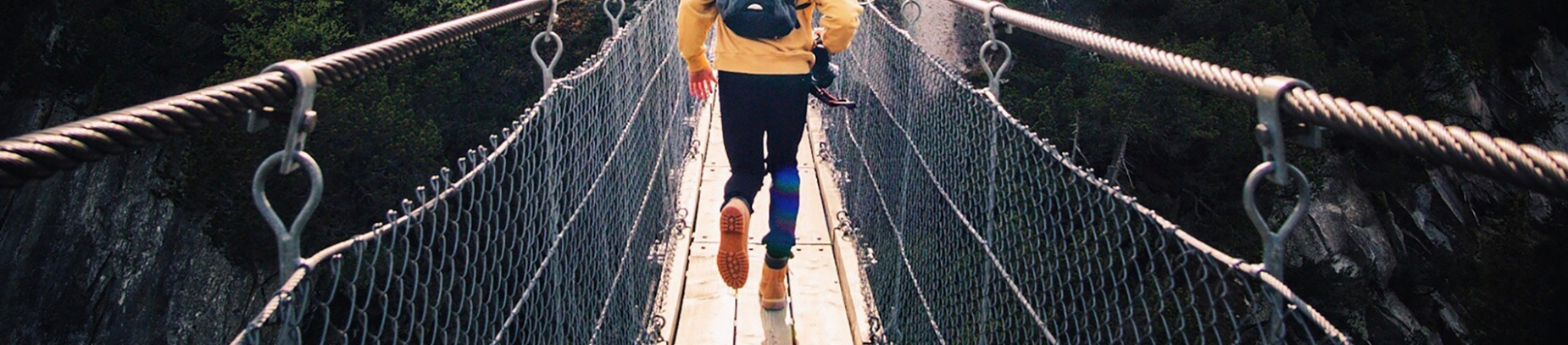 A man in a yellow hoodie running across a rope bridge