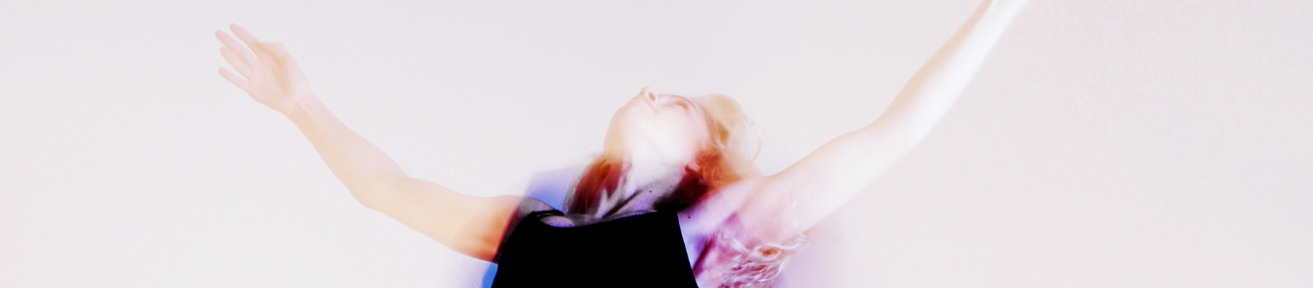 A distorted photo of a women jumping with her hands in the air