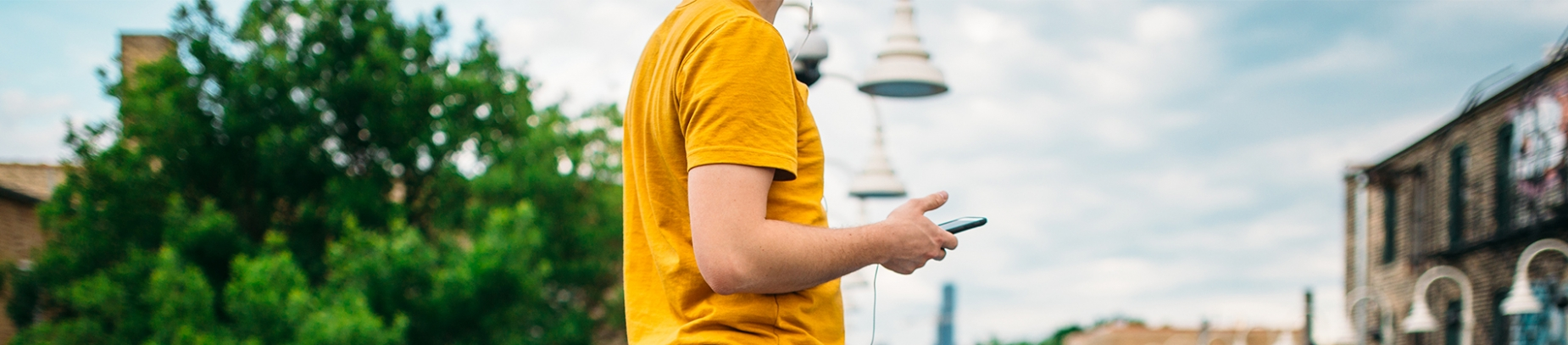 Man in a yellow t-shirt on his phone