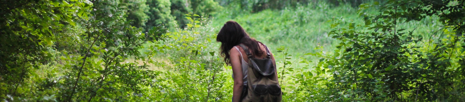 A women walking through a forest wearing a backpack