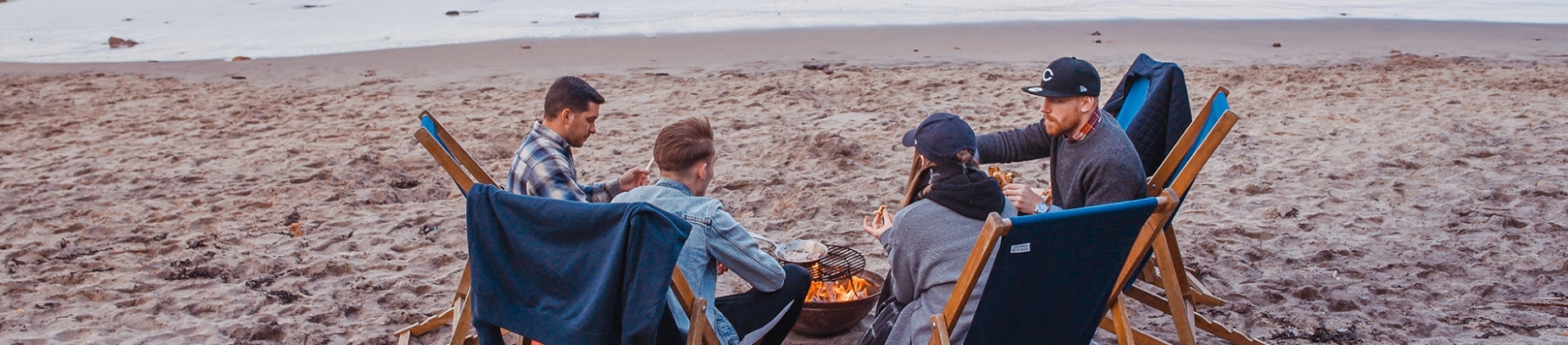 A group of friends sat on the beach around a campfire