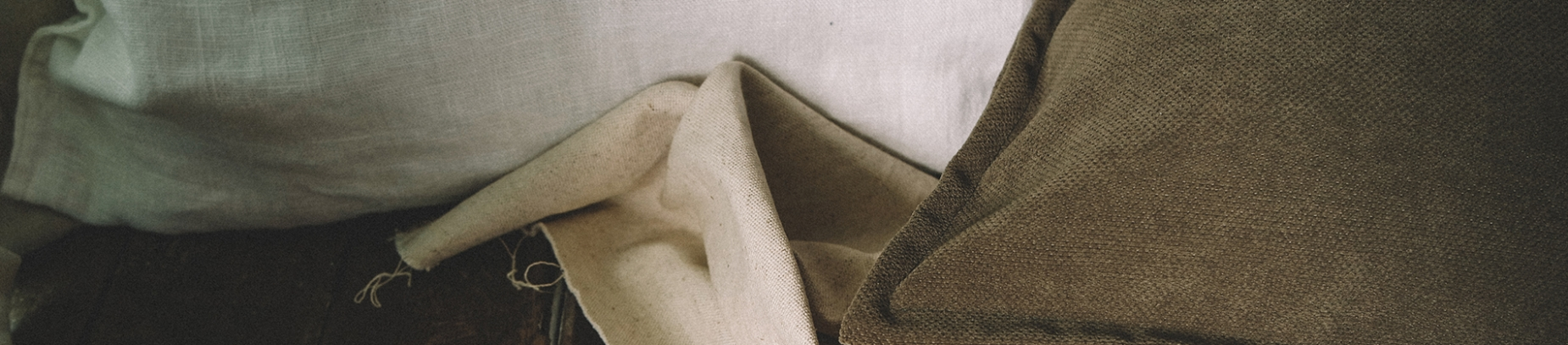 brown pillows and linen on a wooden floor