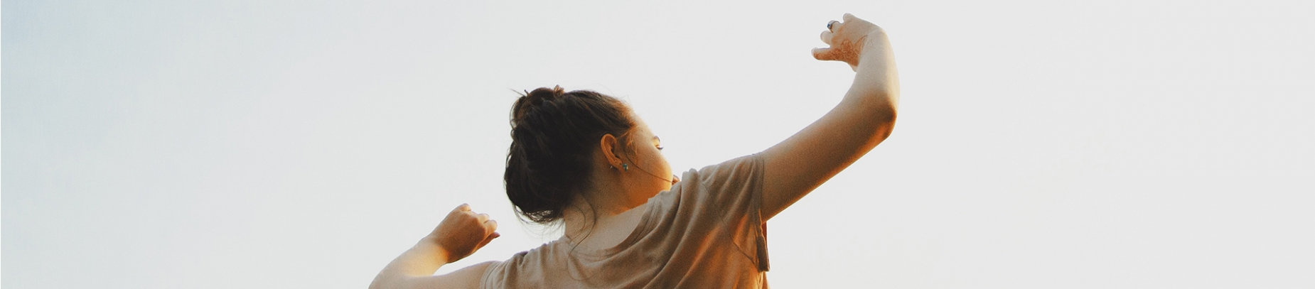A women with her arms in the air towards the sky