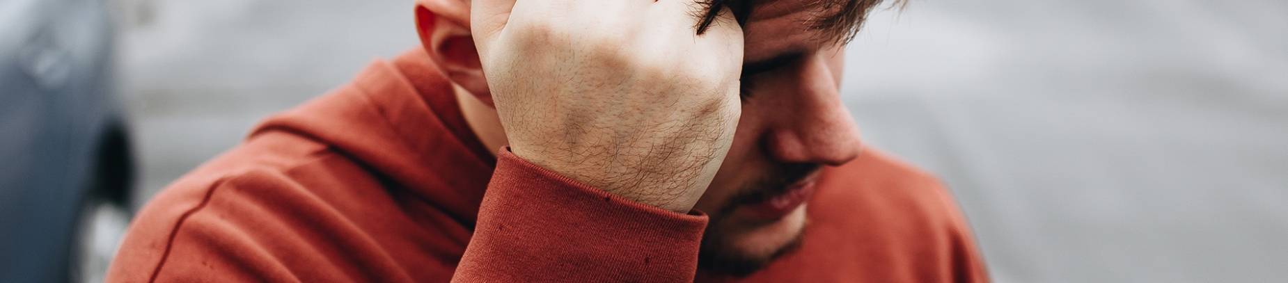 A guy in a red hoodie resting his head on his hand