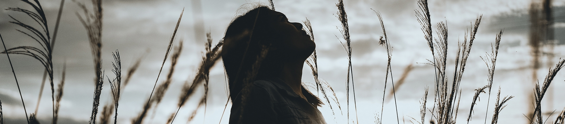 A women stood in a field looking up at the sky