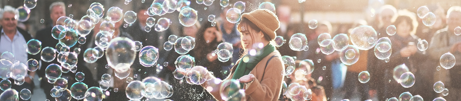 A girl stood in a crowd of people surrounded by bubbles
