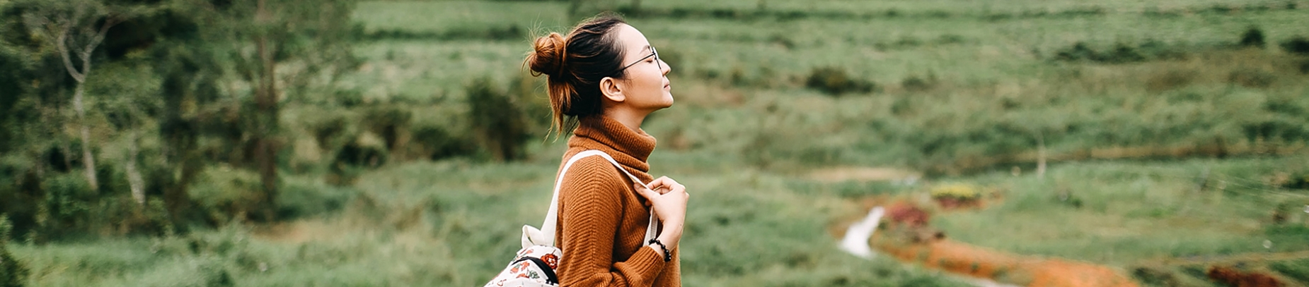A women with a backpack stood in a field with her eyes closed