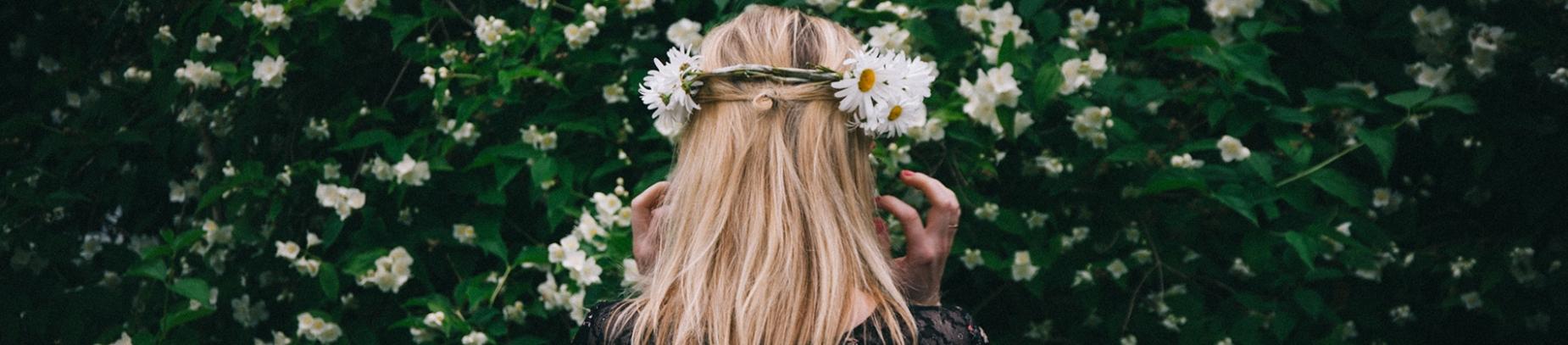 A women facing foliage wearing a flower crown
