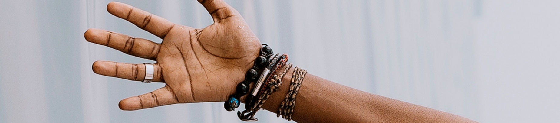 A hand reaching out with bracelets on their wrist