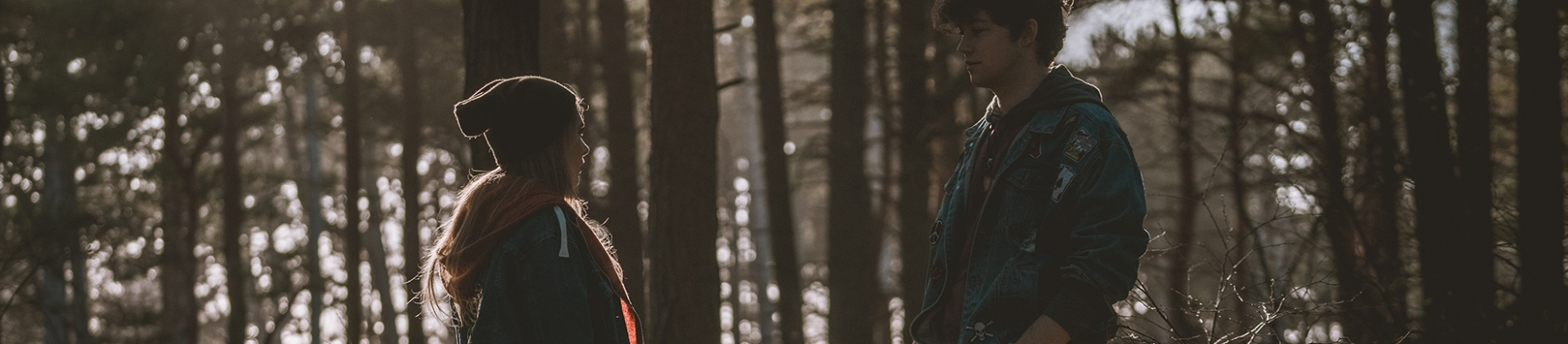 A girl and guy facing each other with a forest behind them